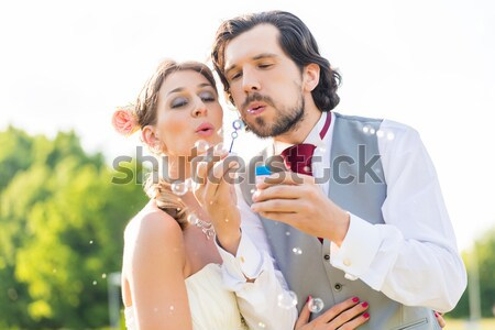 Wedding bride and groom blowing bubbles outside on field Stock photo © Kzenon