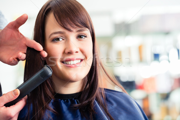 Male coiffeur dress women hair with flat iron in shop Stock photo © Kzenon