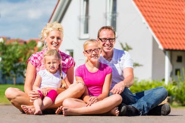 Family sitting on street in front of suburban house Stock photo © Kzenon