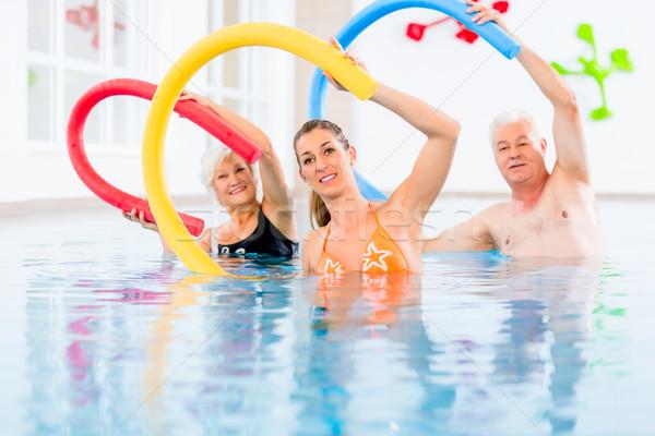 Group in aquarobic fitness swimming pool Stock photo © Kzenon