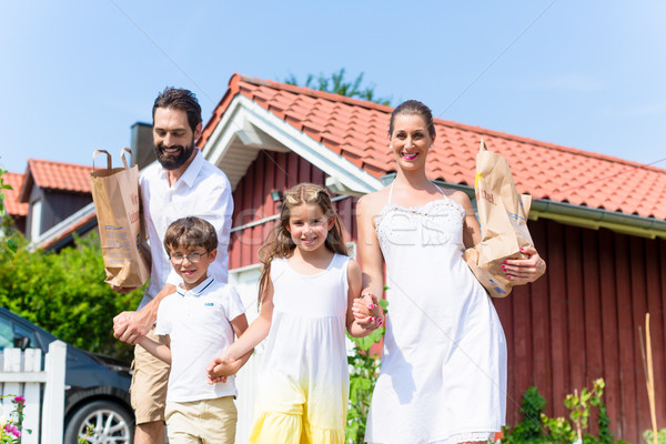 Family coming home from shopping groceries Stock photo © Kzenon