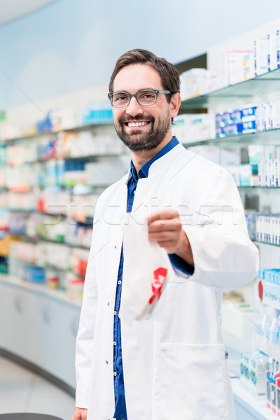 Pharmacist in pharmacy selling pharmaceuticals in bag Stock photo © Kzenon