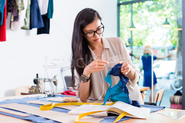 Asian fashion designer woman sewing in her workshop Stock photo © Kzenon