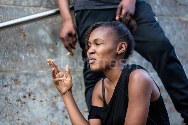 Young African American woman and man smoking outdoors in the cit Stock photo © Kzenon