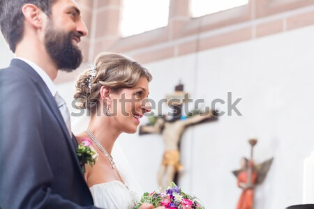 Bride and groom having wedding in church at altar Stock photo © Kzenon