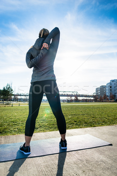 Rear view of a fit woman practicing a shoulder stretch for warmi Stock photo © Kzenon