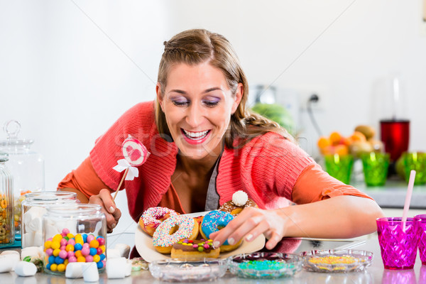 Woman holding candy stick and picking donut Stock photo © Kzenon