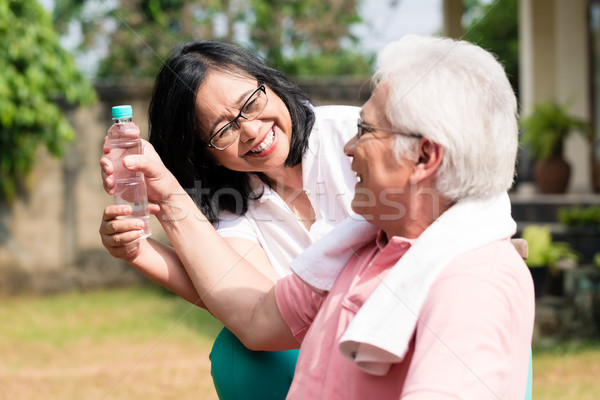 Careful senior woman giving a bottle of water to her partner out Stock photo © Kzenon