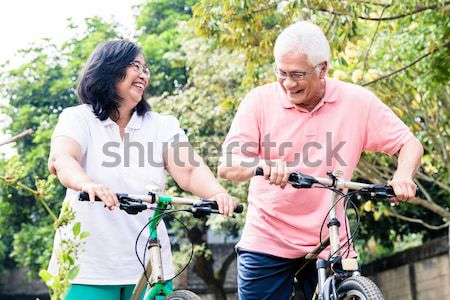Senior wife giving a bottle of water to her husband after cycling Stock photo © Kzenon