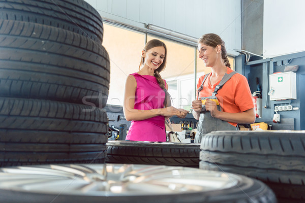 Helpful female auto mechanic checking the identification number of a tire Stock photo © Kzenon