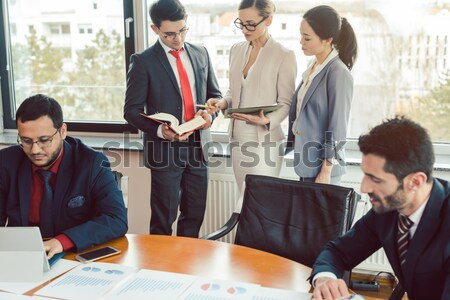 Confident business people smiling while listening to their colleagues Stock photo © Kzenon