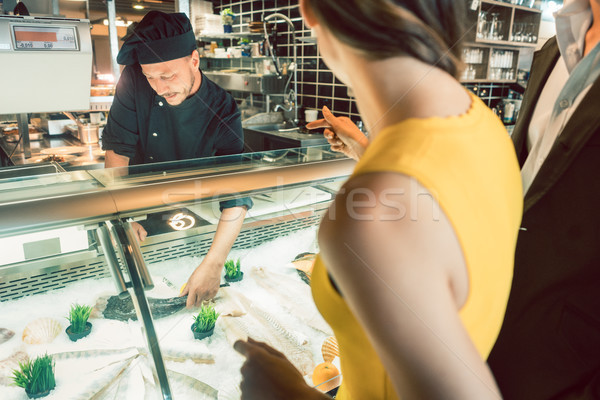 Experienced chef taking a fresh fish from the freezer to cook it Stock photo © Kzenon