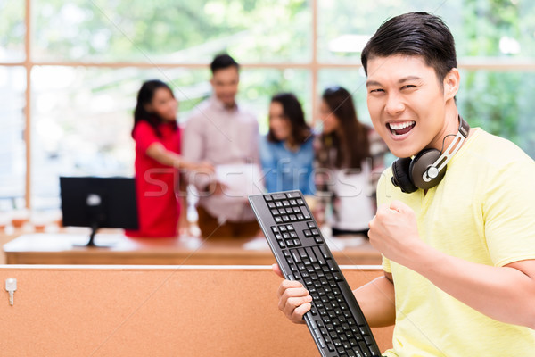 Young Chinese employee happy for his successful work on computer Stock photo © Kzenon