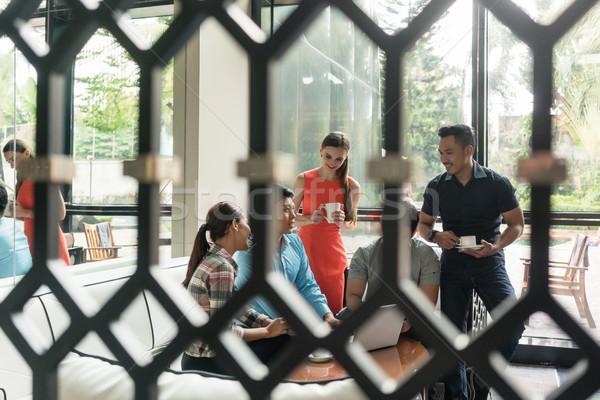 Group of cheerful employees drinking coffee in the lounge area Stock photo © Kzenon