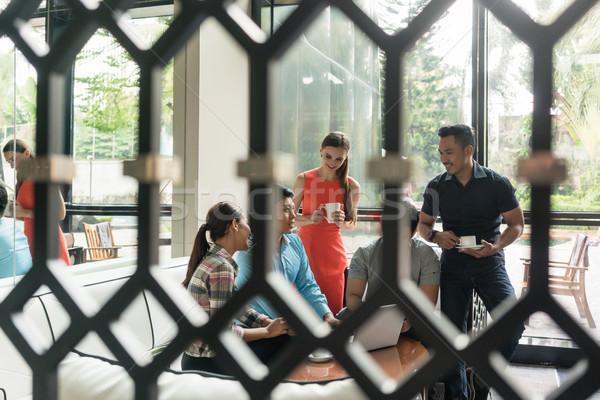 Csoport derűs alkalmazottak iszik kávé társalgó Stock fotó © Kzenon