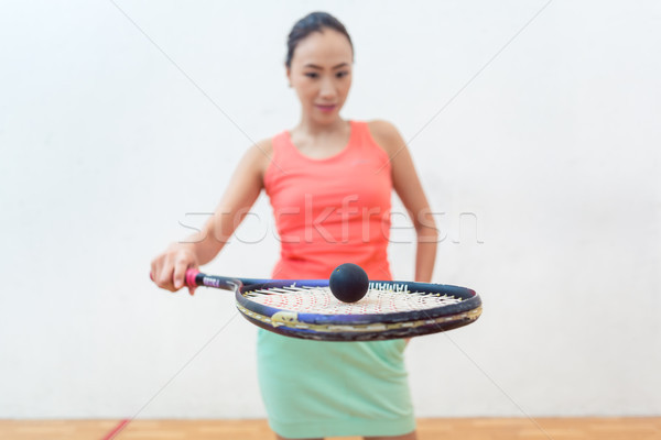 Close-up of a rubber hollow ball on the new squash racket of a fit woman Stock photo © Kzenon