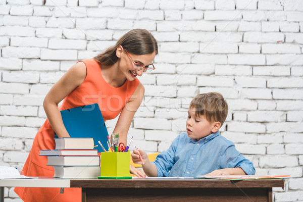 Mother helping her son to do the school homework Stock photo © Kzenon