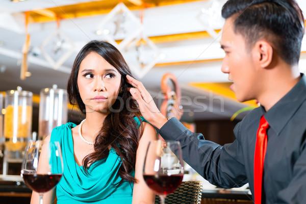 Asian couple sitting in restaurant Stock photo © Kzenon
