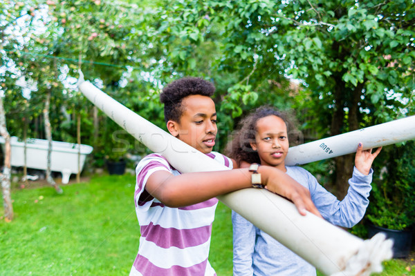 Stock photo: Brother and sister carrying pole in park