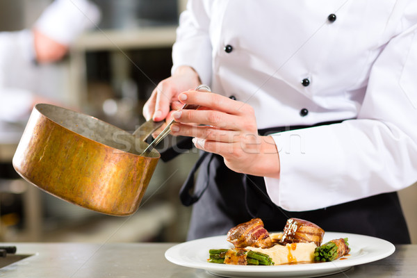 Chef in hotel or restaurant kitchen cooking Stock photo © Kzenon