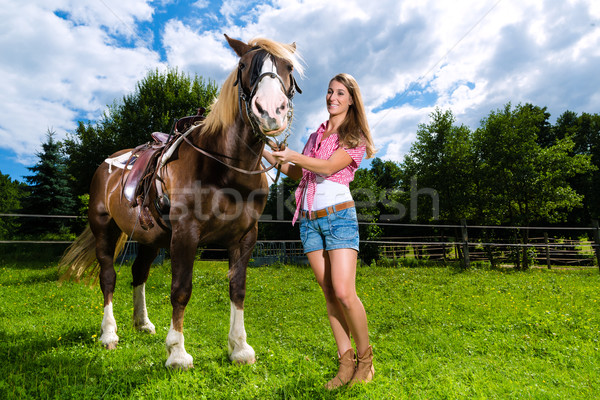 Young woman on the meadow with horse Stock photo © Kzenon