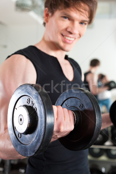 Sport - man is exercising with barbell in gym Stock photo © Kzenon