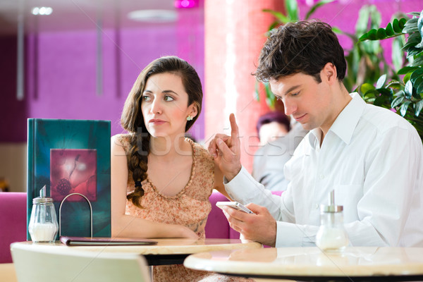 Young couple in cafe not interacting but on phone Stock photo © Kzenon