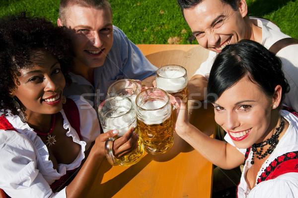 Gruppe vier Freunde Bier Garten vier Personen Stock foto © Kzenon