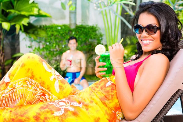 Asian woman tanning at pool with cocktail Stock photo © Kzenon