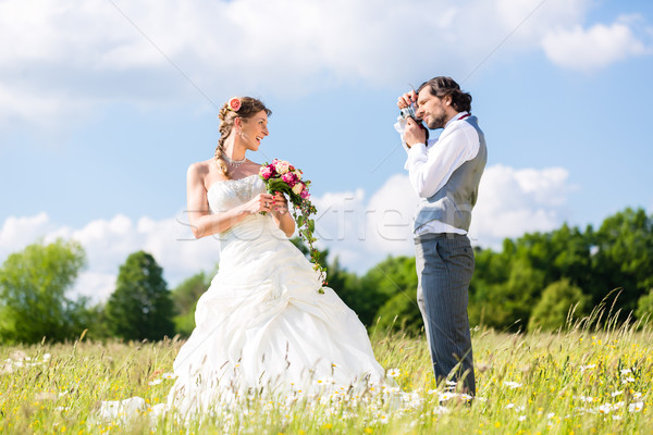Wedding couple taking pictures on meadow Stock photo © Kzenon