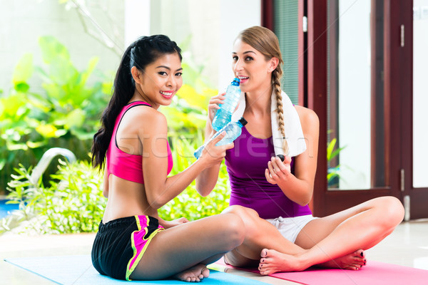 Women friends relaxing after fitness exercise Stock photo © Kzenon