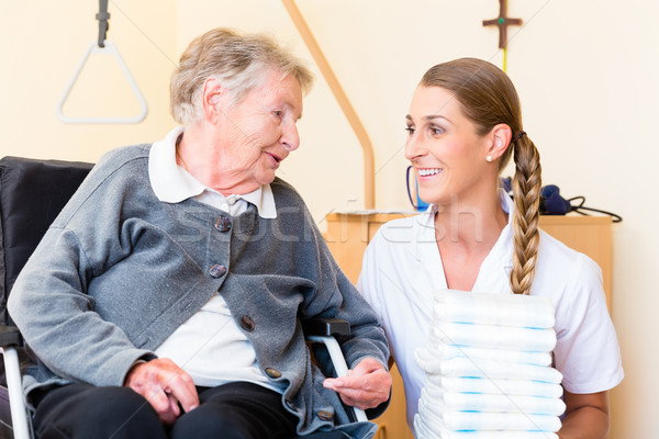 Nurse bringing supplies to woman in retirement home Stock photo © Kzenon