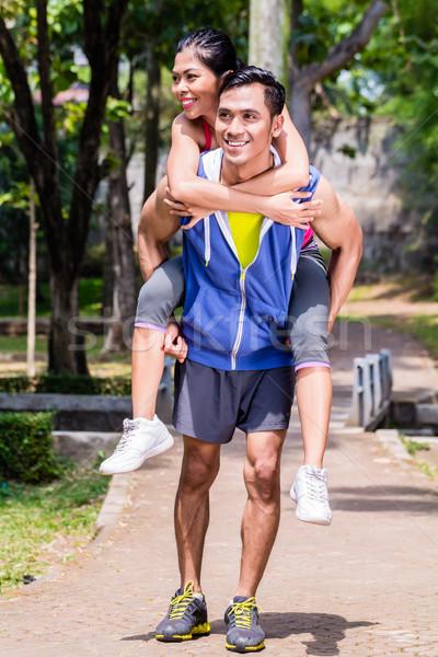 Asian man carrying his girlfriend piggyback for sport Stock photo © Kzenon
