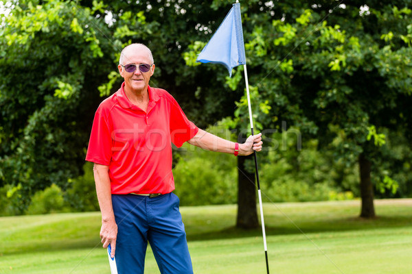 Senior man playing golf on course holding flag Stock photo © Kzenon