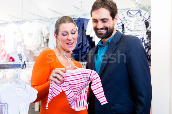 Couple expecting baby buying children wear Stock photo © Kzenon