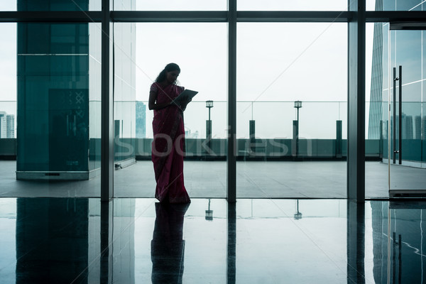 Indian woman using tablet on corridor of modern corporate buildi Stock photo © Kzenon