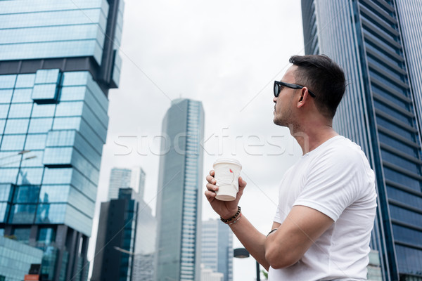Young man looking up to the skyscrapers of a modern business dis Stock photo © Kzenon