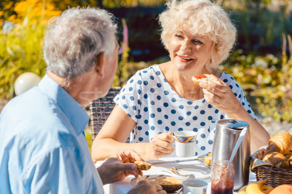 Happy elderly couple eating breakfast in their garden outdoors i Stock photo © Kzenon