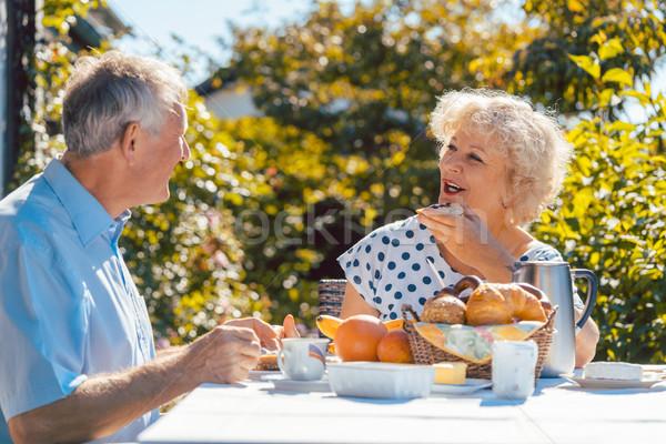 Senior woman and man having breakfast sitting in their garden ou Stock photo © Kzenon