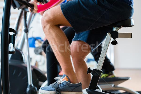 Men doing workout on exercise bike at gym Stock photo © Kzenon