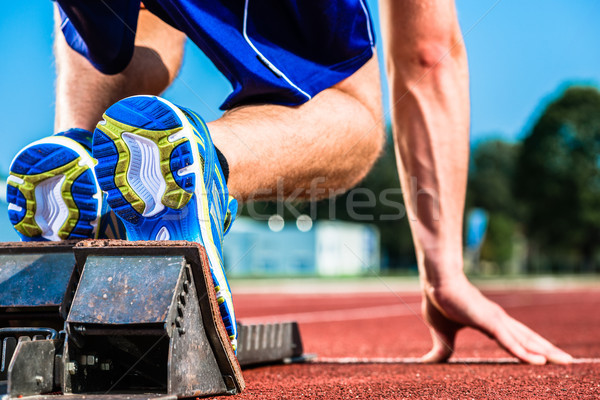 Runner before start signal on starting block of sprint track Stock photo © Kzenon