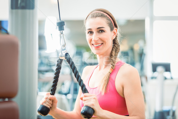 Portrait of a beautiful fit woman smiling while exercising Stock photo © Kzenon