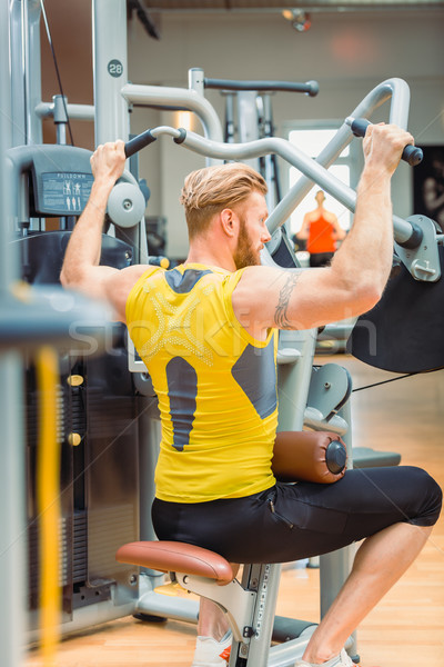 Rear view of a powerful bodybuilder with strong arms exercising at the gym Stock photo © Kzenon