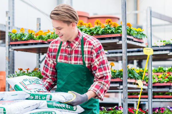 Young man carrying a bag of potting soil during work at the flower market Stock photo © Kzenon