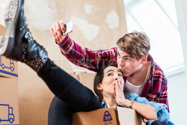 Happy young man and woman making a selfie after moving in together Stock photo © Kzenon