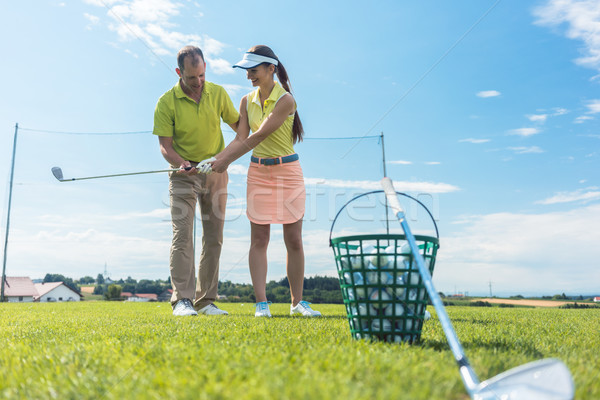 Cheerful young woman learning the correct grip and move for using the golf club Stock photo © Kzenon