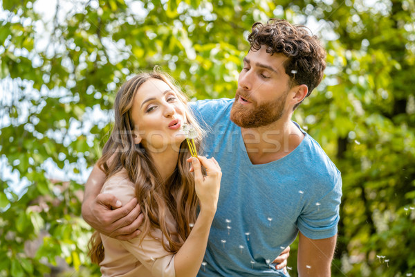 Stock photo: Young couple daydreaming about their future blowing dandelion seeds