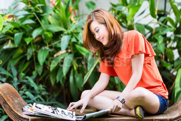 Fiatal ázsiai nő olvas divat magazin Stock fotó © Kzenon