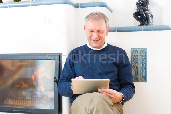 Senior at home in front of fireplace Stock photo © Kzenon