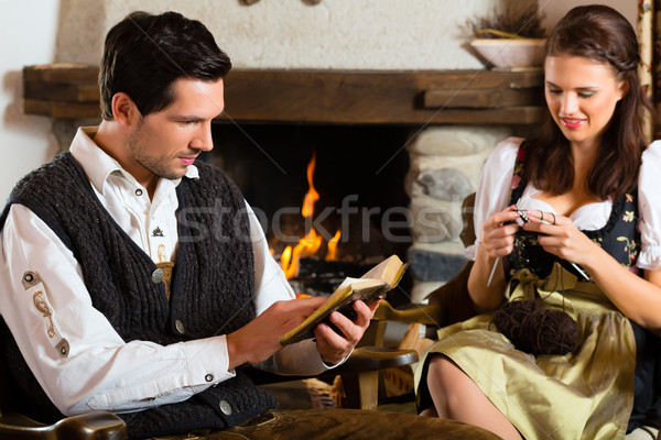 Young couple in mountain hut at fire place Stock photo © Kzenon